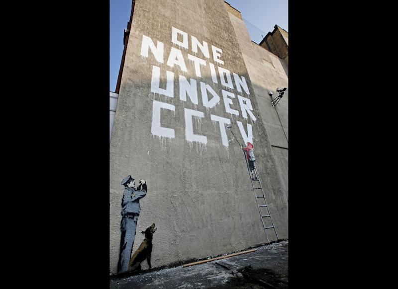 LONDON - APRIL 14: A new Banksy graffiti work on a private property catches the eye of passers by on April 14, 2008 in London, England. The work, which depicts a child painting the words 'One Nation Under CCTV' with a security guard watching him is situated under a security camera and has appeared sometime between the hours of Saturday and Monday morning. (Photo by Cate Gillon/Getty Images)