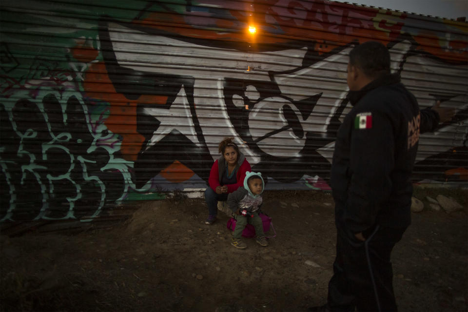 Xinia (19) and her son Kevin (4) talk with Mexican border police after being caught crossing the Mexico-US border wall, December 1, 2018. (Photo: Fabio Bucciarelli for Yahoo News)