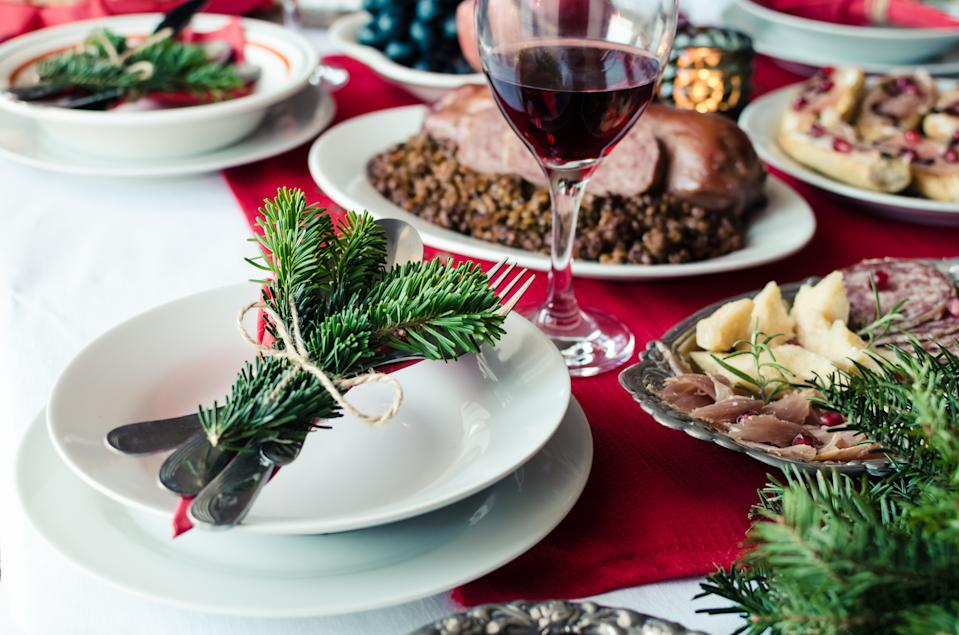 Family together Christmas celebration concept. Festive place setting for holiday dinner with natural decorations from fir tree branches.