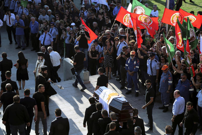 Pallbearers carry the coffin of the former Cyprus' President Dimitris Christofias, as people wave flags of communist party (AKEL) during his state funeral at the Orthodox Christian Church of the Lord's Wisdom in capital Nicosia, Cyprus, Tuesday, June 25, 2019. European communist and left-wing party heads and leaders from ethnically split Cyprus' breakaway Turkish Cypriot community were among those attending a funeral service for the country's former president Christofias. (AP Photo/Petros Karadjias)