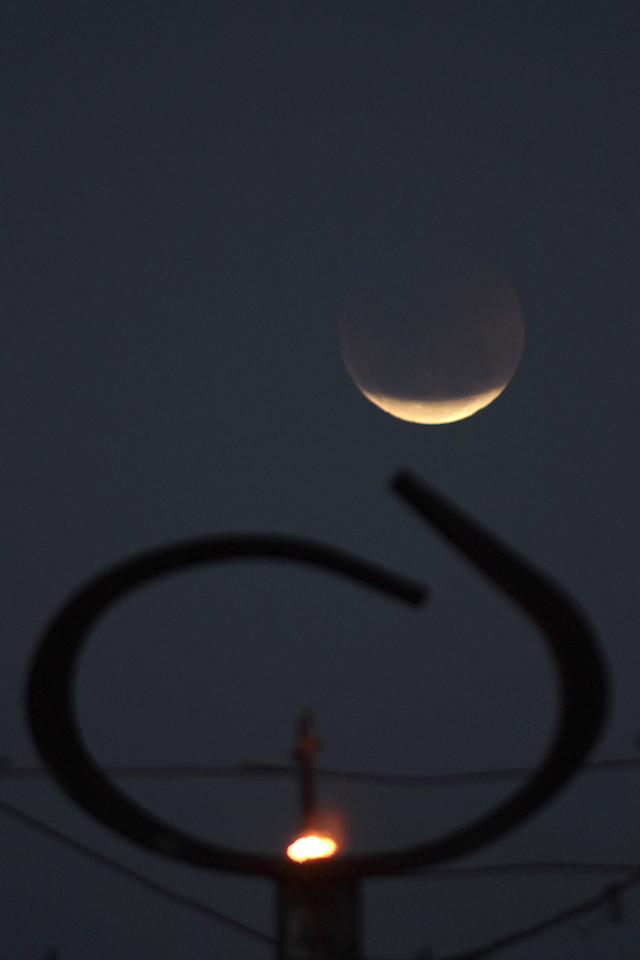 The earth casts its shadow over the moon during a total lunar eclipse seen from behind the Pantheon of Freedom sculpture, featuring a torch, at Three Powers Square in downtown Brasilia, Brazil, Wednesday June 15, 2011. (AP Photo/Eraldo Peres)