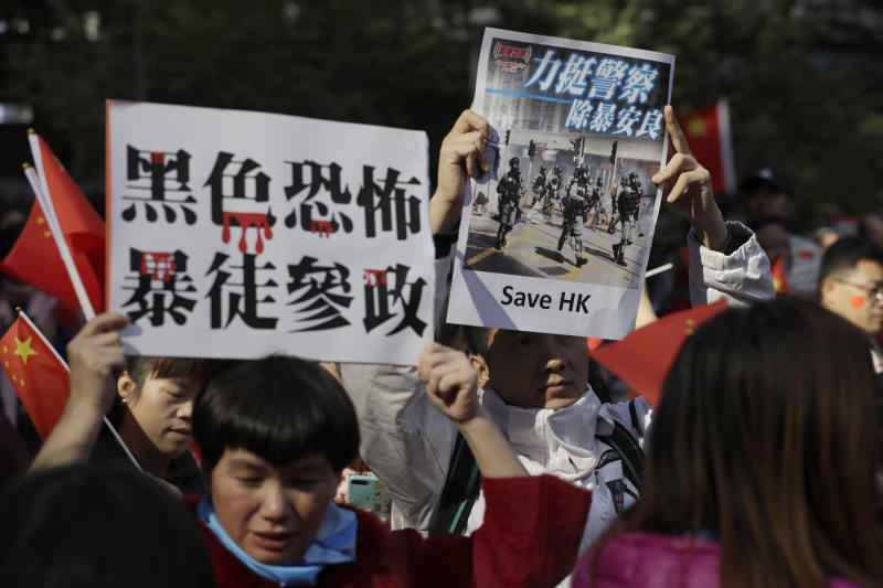 """Pro-Beijing supporters hold up signs which reads """"Black Terror, Rioters involved in politics"""" and """"Support Police, Get rid of Violence"""" during a rally in Hong Kong on Saturday, Dec. 7, 2019. Six months of unrest have tipped Hong Kong's already weak economy into recession. (AP Photo/Mark Schiefelbein)"""