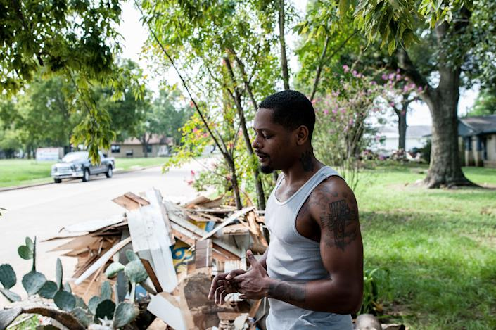 Damion Lasker, 24, stands next to debris on Sunday taken from his mother's flooded home in Katy, Texas, west of Houston. Houses on every street in this town have similar piles waiting for pickup. (Photo: JOSEPH RUSHMORE FOR HUFFPOST)
