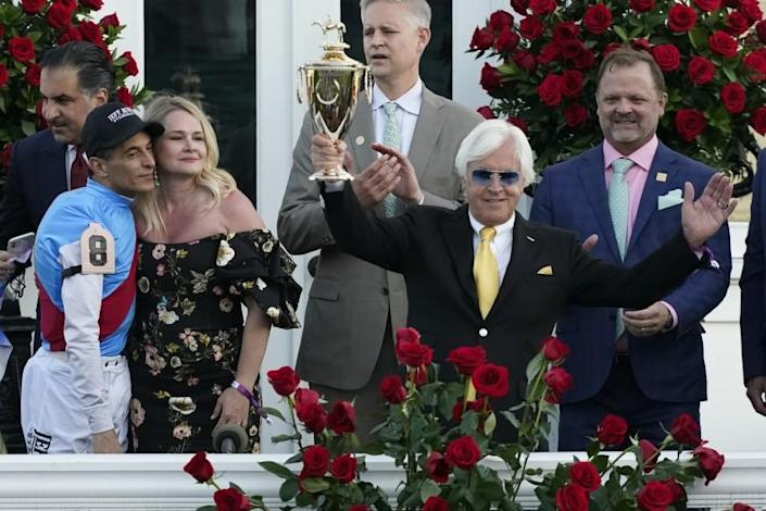 Jockey John Velazquez, left, watches as trainer Bob Baffert holds up the winner's trophy after they victory.