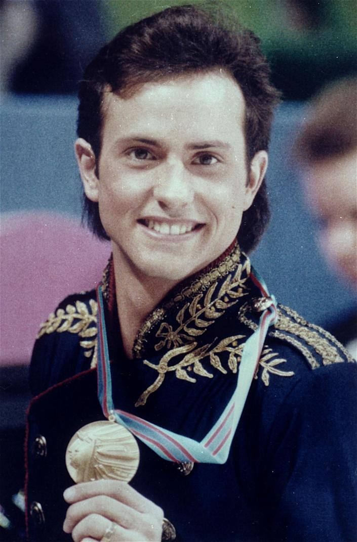 """FILE - In this Feb. 20, 1988 file photo, figure skater Brian Boitano shows off his Olympic gold medal, in Calgary, Alberta. Two days after being named to the U.S. delegation for Sochi, Boitano has announced he is gay. But the 1988 gold medalist says Thursday, Dec. 19, 2013, in a statement that """"being gay is just one part of who I am. ... I hope we can remain focused on the Olympic spirit which celebrates achievement in sport by peoples of all nations."""" (AP Photo/Jack Smith)"""