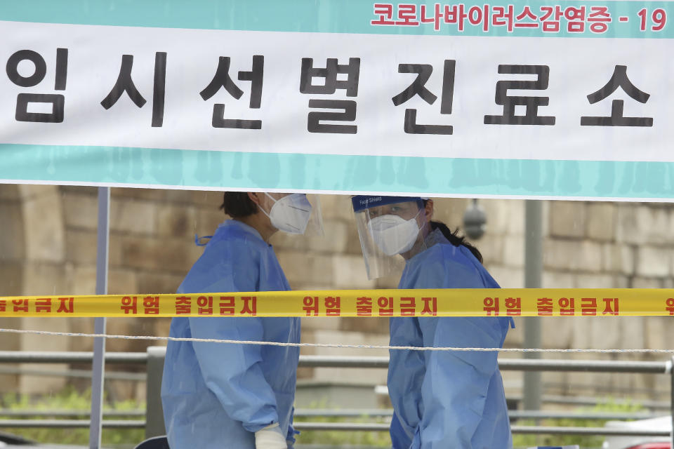 "Health officials wearing protective gear wait for people at a makeshift clinic for COVID-19 testing in Seoul, South Korea, Monday, Aug. 10, 2020. The signs reads; ""A makeshift clinic for COVID-19 test."" (AP Photo/Ahn Young-joon)"