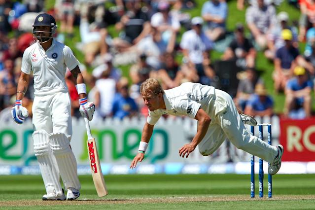 WELLINGTON, NEW ZEALAND - FEBRUARY 15: Neil Wagner of New Zealand loses his footing while bowling as Virat Kohli of India looks on during day two of the 2nd Test match between New Zealand and India on February 15, 2014 in Wellington, New Zealand. (Photo by Hagen Hopkins/Getty Images)