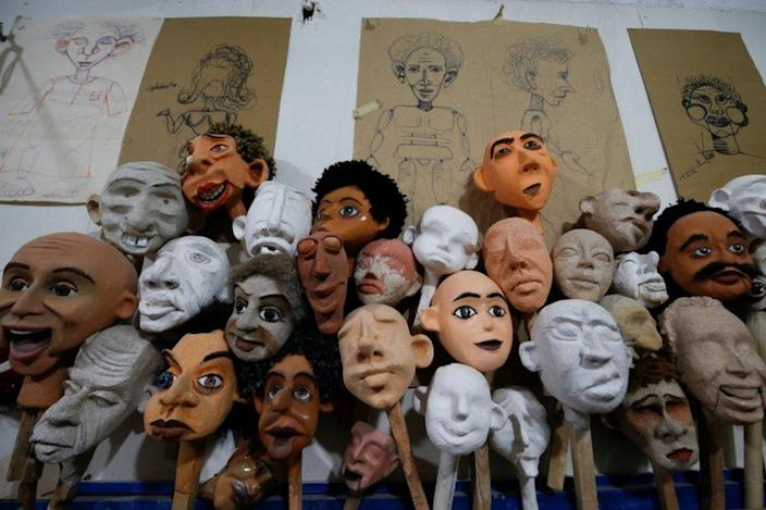 A jumble of handmade puppets of different complexions and facial features, at various stages of completion.