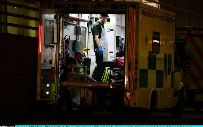 Paramedics wearing PPE prepare to remove a patient from an ambulance at The Royal London Hospital on December 31, 2020  -  Hollie Adams/Getty Images Europe