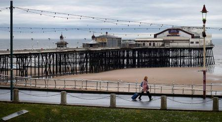 FILE PHOTO: A woman pulls her suitcase past the North Pier in Blackpool, Britain May 16, 2017.  REUTERS/Phil Noble/File Photo