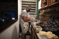 Andres Burgos, a 55-year-old publicist, makes arepas or corn flour patties that he will distribute to the needy, in his home in Caracas, Venezuela, Wednesday, Oct. 21, 2020. Burgos' world was becoming increasingly solitary. The office of his advertising firm was practically empty, due to Venezuela's crushing economic crisis, and many of his relatives had sought a brighter future abroad. So Burgos marshaled his cooking skills to reach out to others. (AP Photo/Ariana Cubillos)