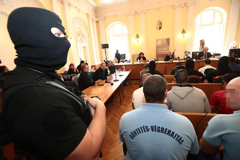 A policeman stands guard in the Hungarian courtroom Thursday as four key suspects are sentenced to 25 years in jail for the gruesome deaths of 71 migrants (AFP Photo/FERENC ISZA)