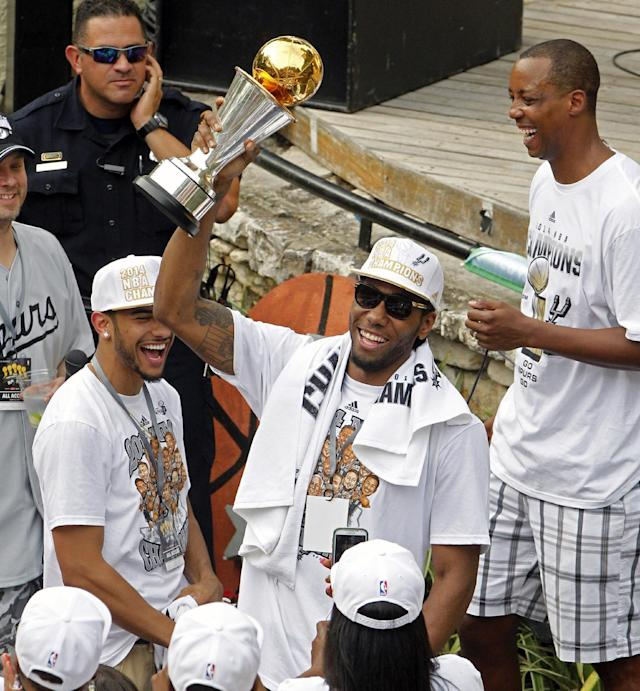 San Antonio's Kawhi Leonard holds up the NBA Finals' Most Valuable Player trophy during the Spurs' parade and celebration of the Spurs' 5th NBA Championship in San Antonio, Texas, Weds., June 18, 2014. (AP Photo/Michael Thomas)