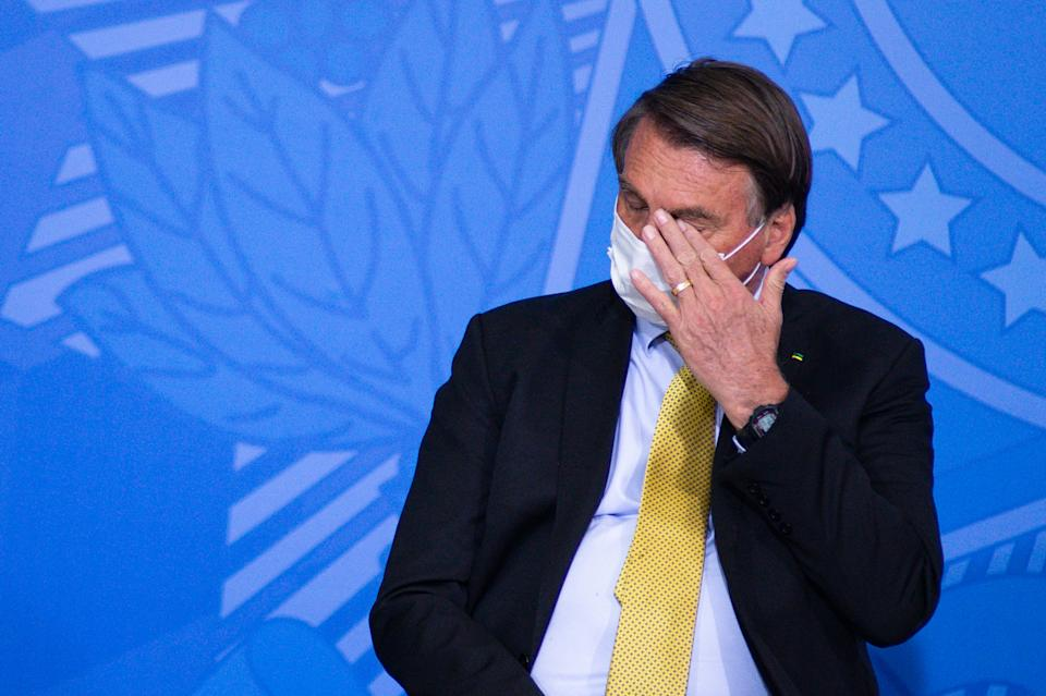 BRASILIA, BRAZIL - JUNE 29: President of Brazil Jair Bolsonaro touches his face during an event to launch a new register for professional workers of the fish industry at Planalto Government Palace on June 29, 2021 in Brasilia, Brazil. Health Minister, Marcelo Queiroga, announced after the event and in conversation with journalists, that the contract with the Covaxin vaccine is suspended. (Photo by Andressa Anholete/Getty Images)
