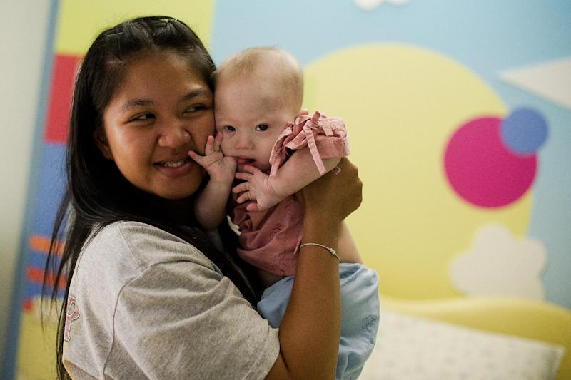 Thai surrogate mother Pattaramon Chanbua (L) holds her baby Gammy, born with Down Syndrome, at the Samitivej hospital in Chonburi province on August 4, 2014