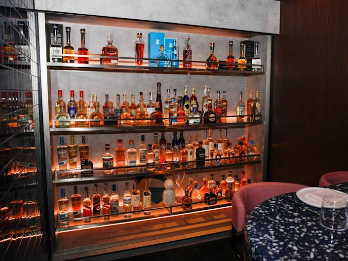 a wall of hard liquor by a dining table