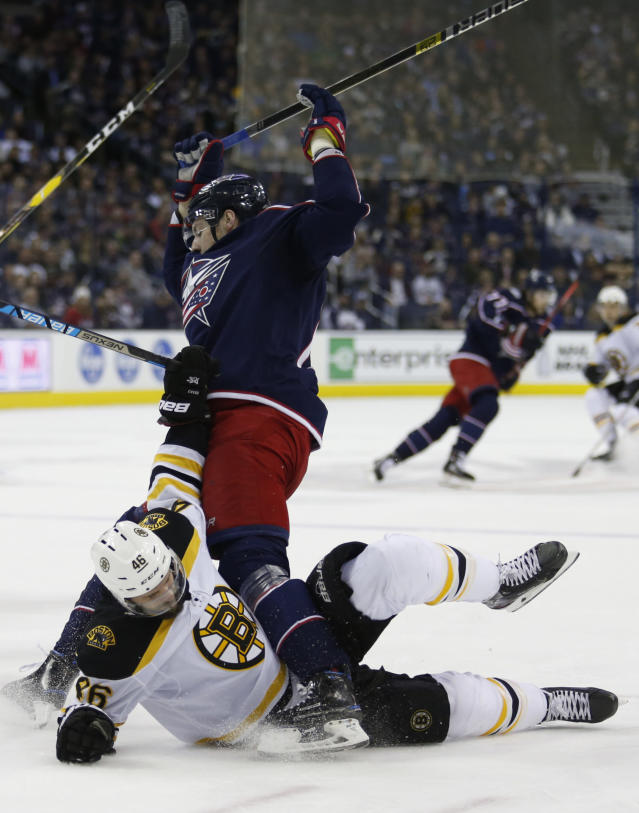 Boston Bruins forward David Krejci, bottom, of the Czech Republic, gets tangled with Columbus Blue Jackets forward Pierre-Luc Dubois during the first period of an NHL hockey game in Columbus, Ohio, Tuesday, April 2, 2019. (AP Photo/Paul Vernon)