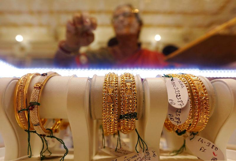 Gold bangles are on display as a woman makes choices at a jewellery showroom during Dhanteras in Kolkata