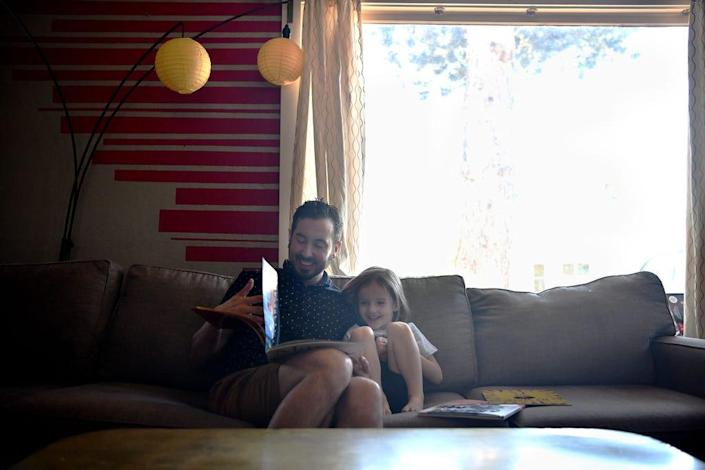 Trystan Reese and his son Leo, 3, read books together at home in Portland, Oregon, on May 16, 2021.