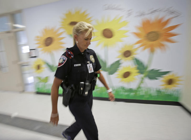 In this photo taken Thursday, Aug. 22, 2013, Dara Van Antwerp, the school resource officer at Panther Run Elementary School Pembroke Pines, Fla. walks the hallways of the school where she teaches in the Gang Resistance And Drug Education (GRADE) program in the Fort Lauderdale suburb. The armed school resource office will be permanently stationed on campus despite the decline in crime in this middle-class community. The decision comes in the wake of the Sandy Hook Elementary School shooting in Connecticut. (AP Photo/Wilfredo Lee)