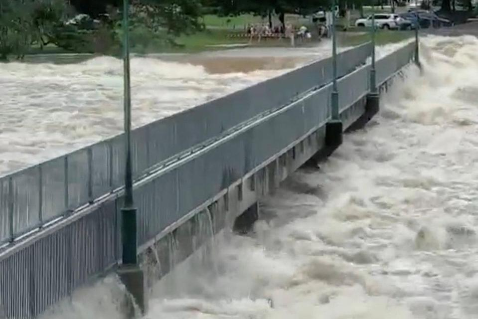 Floodwater flows by the Aplins Weir Rotary Park footbridge in Mundingburra district on Sunday. Source; Reuters