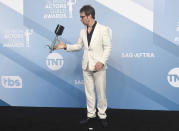 """Sam Rockwell flips his award for outstanding performance by a male actor in a television movie or miniseries for """"Fosse/Verdon"""" in the press room at the 26th annual Screen Actors Guild Awards at the Shrine Auditorium & Expo Hall on Sunday, Jan. 19, 2020, in Los Angeles. (Photo by Jordan Strauss/Invision/AP)"""
