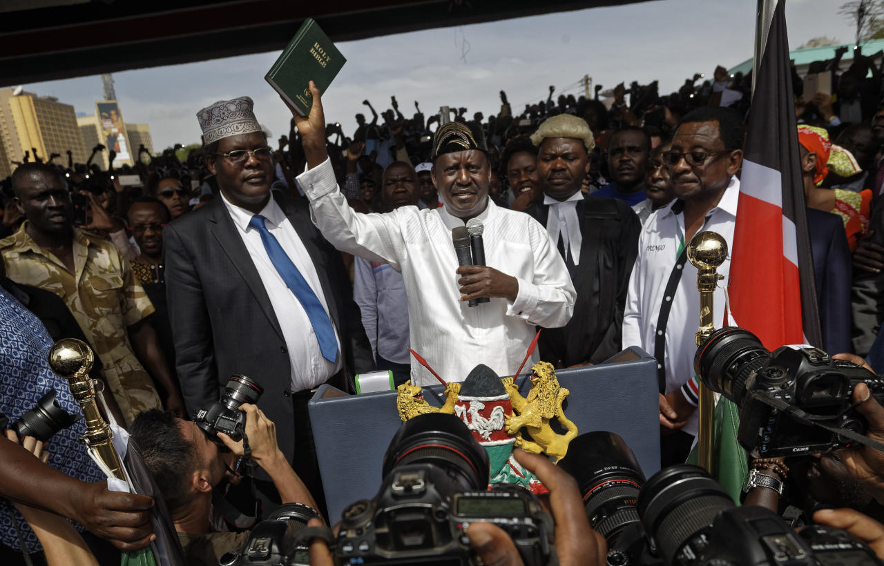 "<p>Opposition leader Raila Odinga holds a bible aloft after swearing an oath during a mock ""swearing-in"" ceremony at Uhuru Park in downtown Nairobi, Kenya Tuesday, Jan. 30, 2018. (Photo: Ben Curtis/AP) </p>"