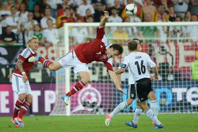 Danish midfielder William Kvist (C) goes airborne next to German defender Philipp Lahm during the Euro 2012 football championships match Denmark vs. Germany, on June 17, 2012 at the Arena Lviv in Lviv.     TOPSHOTS/AFP PHOTO/ANNE-CHRISTINE POUJOULATANNE-CHRISTINE POUJOULAT/AFP/GettyImages