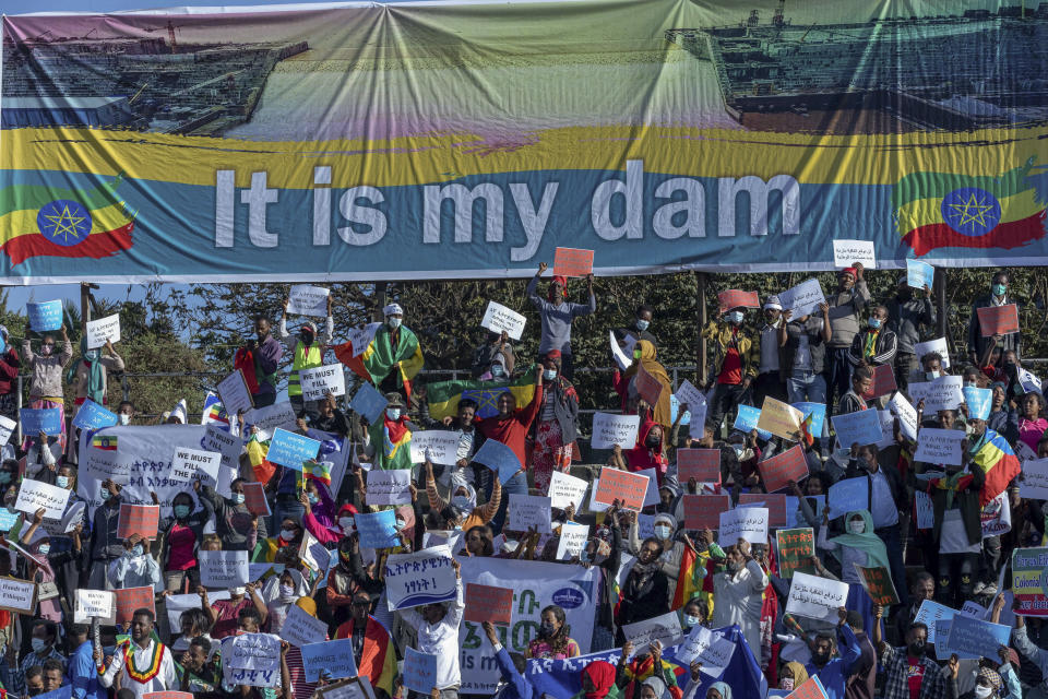 Ethiopians protest against international pressure on the government over the conflict in Tigray, below a banner referring to The Grand Ethiopian Renaissance Dam, at a demonstration organised by the city mayor's office held at a stadium in the capital Addis Ababa, Ethiopia Sunday, May 30, 2021. Thousands of Ethiopians gathered Sunday to protest outside pressure on the government over its brutal war in Tigray, after the U.S. said last week it has started restricting visas for government and military officials of Ethiopia and Eritrea who are seen as undermining efforts to resolve the fighting. (AP Photo/Mulugeta Ayene)