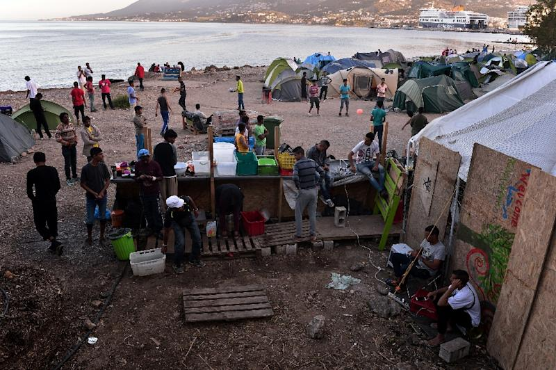 Migrants sit at a makeshift camp staged near the port of Mytilene on the Greek island of Lesbos on April 15, 2016 (AFP Photo/Louisa Gouliamaki)