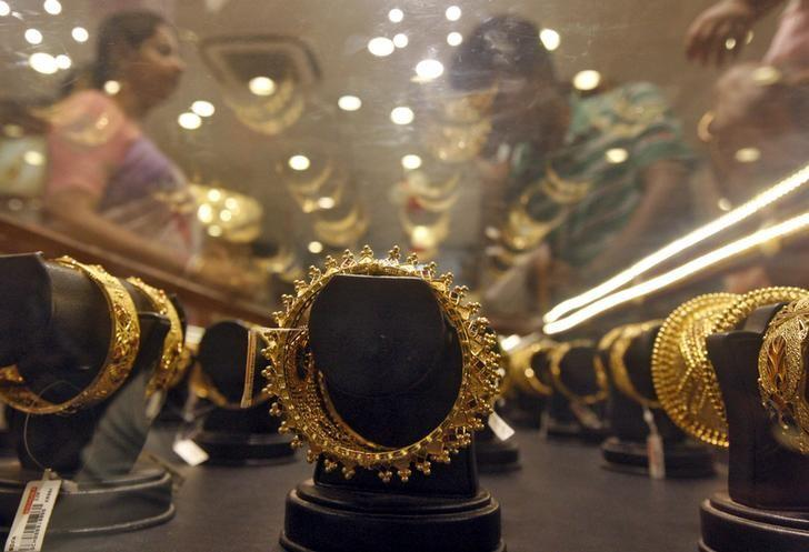 Gold bracelets are on display as a woman makes choices at a jewellery showroom in Kolkata