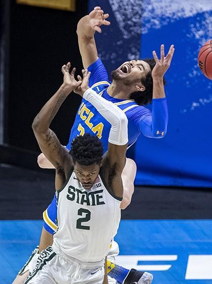 Michigan State's Rocket Watts, foreground, and UCLA's Johnny Juzang battle for a rebound in the first half Thursday.