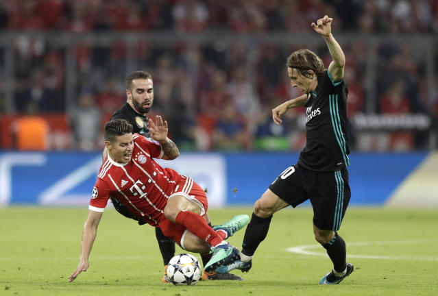 Bayern's James, center, is challenged by Real Madrid's Daniel Carvajal, back, and Luka Modric, right, during the semifinal first leg soccer match between FC Bayern Munich and Real Madrid at the Allianz Arena stadium in Munich, Germany, Wednesday, April 25, 2018. (AP Photo/Matthias Schrader)