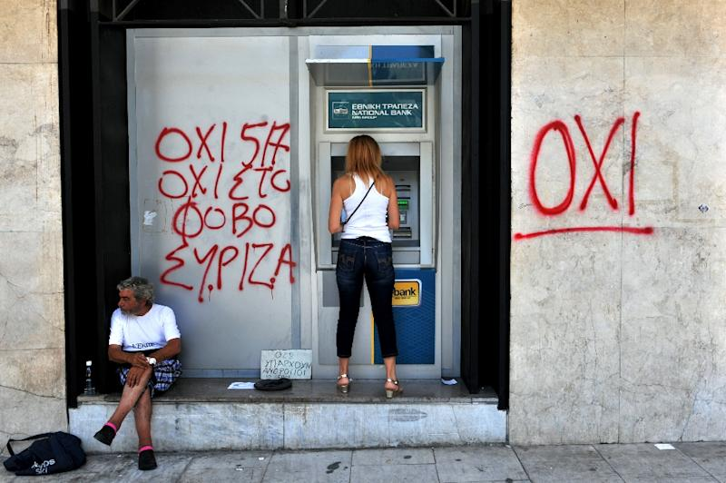 "Five years of economic crisis in Greece has had devastating social consequences, with many forced on to the streets as unemployment has soared to 26 per cent The financial crisis that has devastated Greece has push them onto the streets. A woman withdraws money from an ATM machine next to a beggar and a graffiti reading"" No to fear"" in Thessaloniki on July 6, 2015. More than 61 percent of Greek voters rejected fresh austerity demands by the country's EU-IMF creditors in a historic referendum, official results from over 95 percent of polling stations showed. AFP PHOTO / SAKIS MITROLIDIS (AFP Photo/Sakis Mitrolidis)"