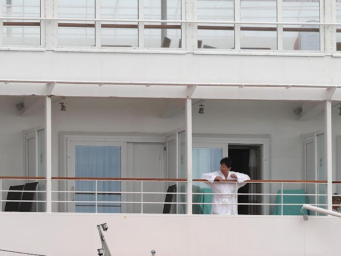 A passenger on the MV Artania look out from their rooms in Fremantle on March 27, 2020.