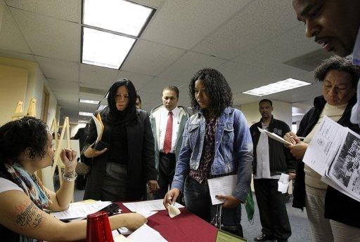 Job seekers wait in line to meet with a recruiter during a job fair