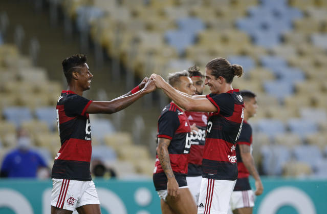 Flamengo's Bruno Henrique, left, celebrates with teammate Filipe Luis after scoring during a Rio de Janeiro soccer league match against Bangu at the Maracana stadium in Rio de Janeiro, Brazi, Thursday, June 18, 2020. Rio de Janeiro's soccer league resumed after a three-month hiatus because of the coronavirus pandemic. The match is being played without spectators to curb the spread of COVID-19. (AP Photo/Leo Correa)