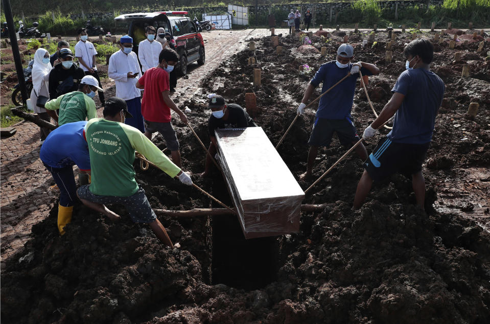 Workers lower a coffin into a grave during a burial at the special section of Jombang Public Cemetery reserved for those who died of COVID-19, in Tangerang on the outskirts of Jakarta, Indonesia, Monday, June 21, 2021. Indonesia saw significant spikes in confirmed COVID-19 cases recently, an increase blamed on travel during last month's Eid al-Fitr holiday as well as the arrival of new virus variants, such as the the Delta version first found in India. (AP Photo/Tatan Syuflana)