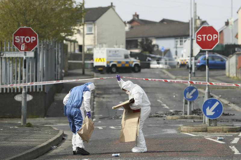 Police forensic officers at the scene in Londonderry, Northern Ireland, Friday April 19, 2019, following the death of 29-year-old journalist Lyra McKee who was shot and killed during overnight rioting. Police in Northern Ireland said Friday they are investigating the fatal shooting of a journalist during overnight rioting in the city of Londonderry. (Brian Lawless/PA via AP)