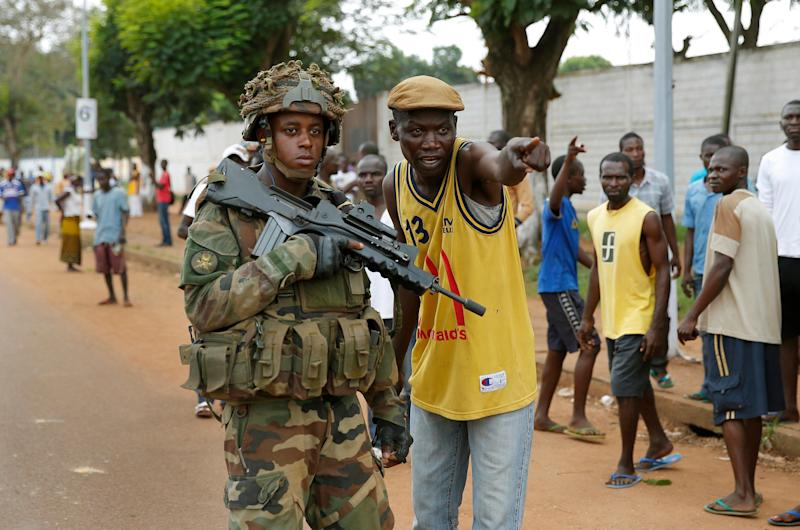 A Christian man points suspected Seleka members to a French soldier in Bangui, Central African Republic, Monday Dec. 9, 2013. Both Christian and Muslim mobs went on lynching sprees as French Forces deployed in the capital. French forces fired warning shots to disperse the crowds. (AP Photo/Jerome Delay)
