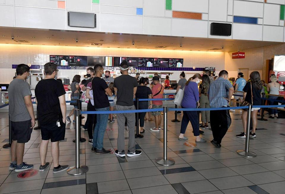 <p>Customers line up to buy snacks at the concession stand at AMC Town Square 18 on August 20 in Las Vegas, Nevada.</p>