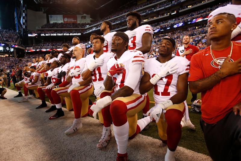 The San Francisco 49ers kneel and stand togetherwhile the national anthem plays prior totheir game against the Indianapolis Colts onOct.8.