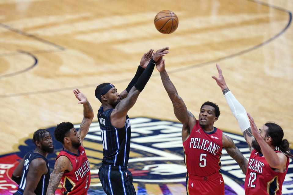 Orlando Magic guard Terrence Ross (31) shoots between New Orleans Pelicans guard Nickeil Alexander-Walker (6), guard Eric Bledsoe (5) and center Steven Adams (12) during overtime in an NBA basketball game in New Orleans, Thursday, April 1, 2021. The Magic won 115-110. (AP Photo/Gerald Herbert)