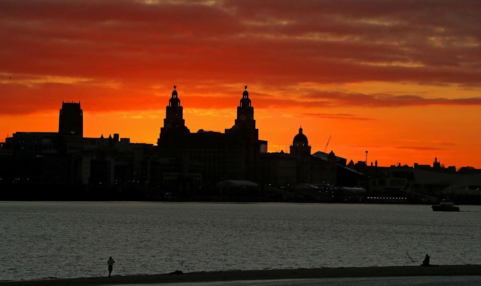 The sun rising behind the Liver Building over the Liverpool waterfront (Peter Byrne/PA) (PA Wire)