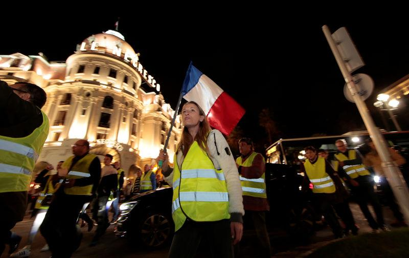 Protesters wearing yellow vests, a symbol of a French drivers' protest against higher fuel prices, attend a demonstration in front of the Negresco Hotel ahead of a nationwide protest, in Nice, France,