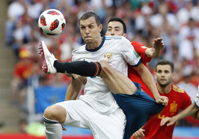 FILE - In this Sunday, July 1, 2018 file photo Russia's Artyom Dzyuba, front , and Spain's Sergio Busquets challenge for the ball during the round of 16 match between Spain and Russia at the 2018 soccer World Cup at the Luzhniki Stadium in Moscow, Russia. (AP Photo/Antonio Calanni, File)
