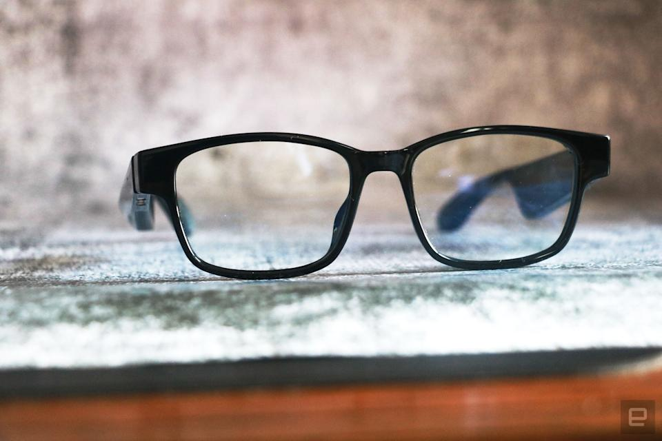 Razer Anzu smart glasses review photo. Slightly left side angled view of the Razer smart glasses sitting on a desk with arms unfolded.