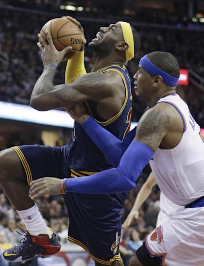 LeBron James, going to the bucket against Carmelo Anthony, likes being a power player off the court as well. (AP)