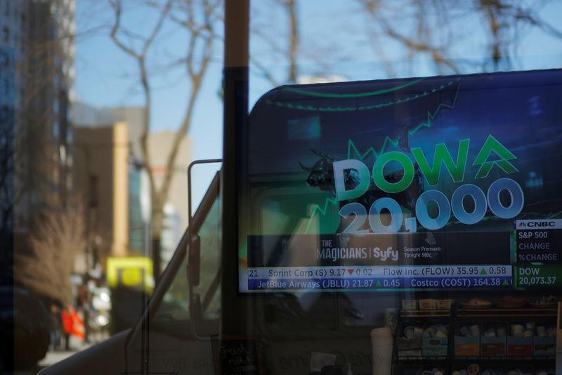 News of the Dow Jones Industrial average passing 20,000 plays on television at a Fidelity Investments office in Cambridge