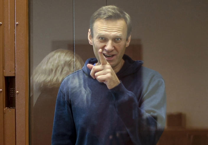 In this photo taken from a footage provided by the Babuskinsky District Court Tuesday, Feb. 16, 2021, Russian opposition leader Alexei Navalny gestures during a hearing on his charges for defamation in the Babuskinsky District Court in Moscow, Russia. Navalny is accused of defaming a World War II veteran who was featured in a video last year advertising constitutional amendments that allowed an extension of President Vladimir Putin's rule. (Babuskinsky District Court Press Service via AP)